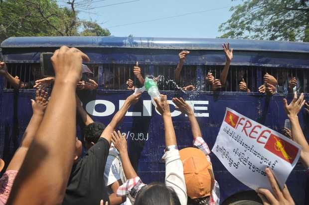 Myanmar student protesters and activists gesture from a departing police truck following a court hearing in Letpadan on April 7, 2015.