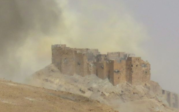 Smoke billows from the Palmyra citadel as Syrian troops retake the ancient city from Islamic State.