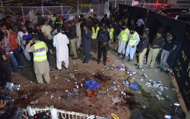 Pakistani rescuers and officials gather at the bomb blast site in Lahore.