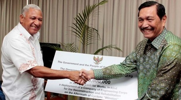 Fiji Prime Minister Frank Bainimarama receives a 5 million US dollar cheque from Indonesia's Coordinating Political, Legal and Security Affairs Minister Luhut Pandjaitan.