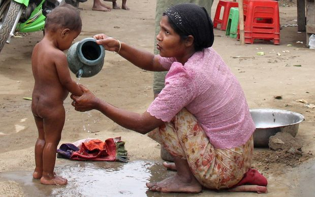 A mother tips water over a toddler who stands naked on a dirt path