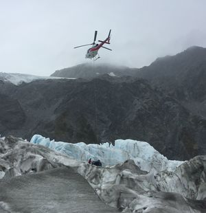 A mountaineer prepares helicopter wreckage for lifting from Fox Glacier.