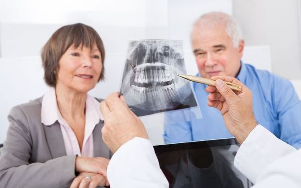 A dentist showing an x-ray to an older couple