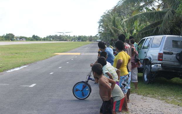 Children watch as a small plane comes in to land at Funafuti airport in Tuvalu.