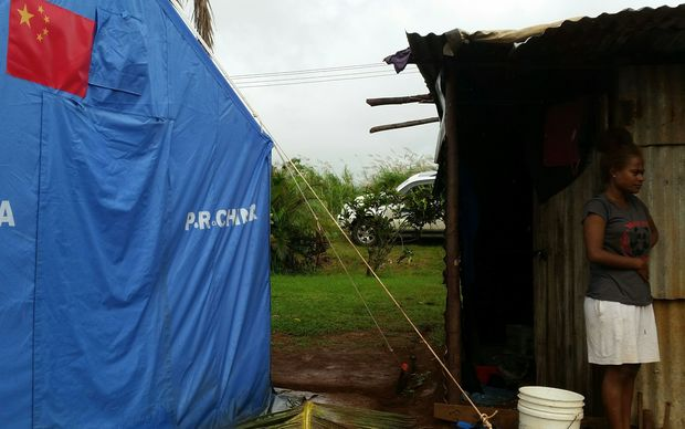 A tent helps to keep a family dry near Lautoka. Thousands are still living in crowded, makeshift shelters.