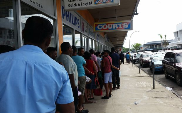People queue in Lautoka for their Fiji National Provident Fund cheques as part of cyclone relief