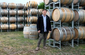 Nik Mavromatis of Muddy Water vineyard beside $1000 French oak barrels.