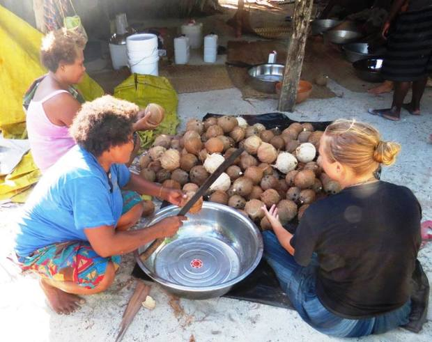 Stage one of making Virgin Coconut Oil, cracking the nuts at Ngadeli village, Reef Islands.