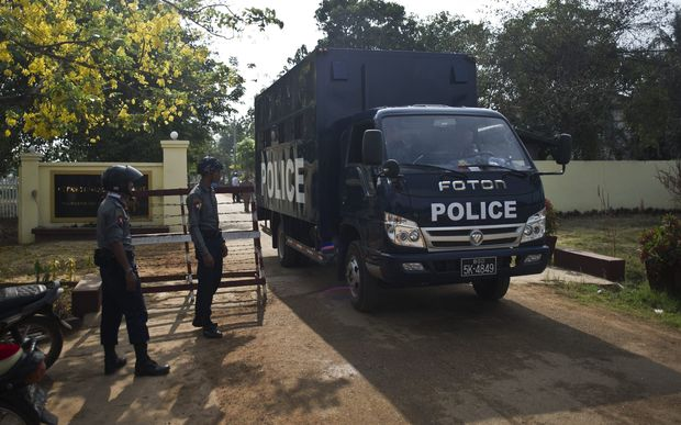 A prison truck and police officers stand guard in front of Tharrawady Central Prison following a prisoners' release in Tharrawady town, Bago Region in Myanmar.