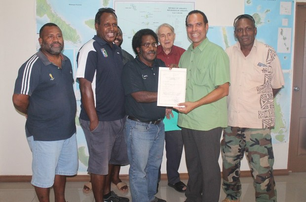 Vanuatu's Minister of Lands Ralph Regenvanu (green shirt) hands over the first negotiator's certificate to be issued for a lease application for rural customary land, to the Vanuatu Football Federation.