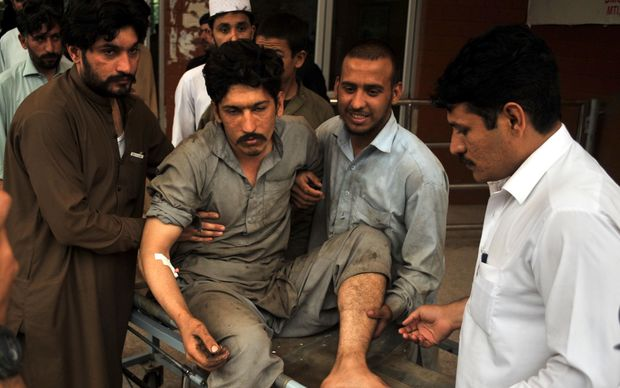 People carry an injured victim to a hospital in the northwestern city of Peshawar, Pakistan.