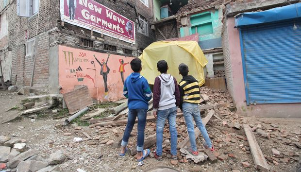 Children look towards a damaged residential structure in Srinagar, the summer capital of Indian-controlled Kashmir.