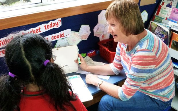 A teacher's aide sit beside a pupil she is helping with writing