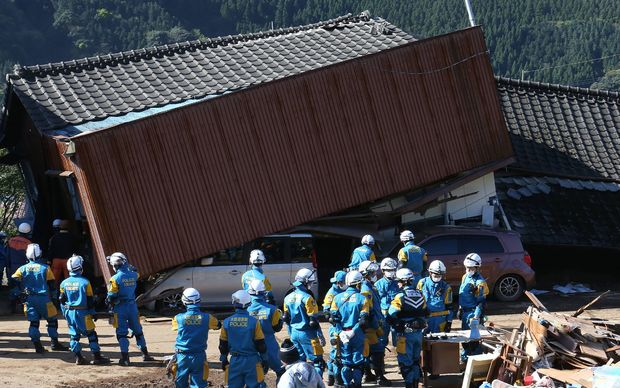 Rescue workers try to save people from a collaspsed house in Mimami-Aso, Kuammoto prefecture in Japan following another large earthquake in days.