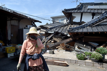 A woman stands in front of her damaged house in Mashiki, Kumamoto prefecture after a 6.5 magnitude quake struck the southwestern island of Kyushu on April 14.