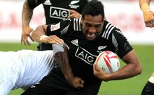 The All Black Sevens' Siona Molia is tackled by a French man.