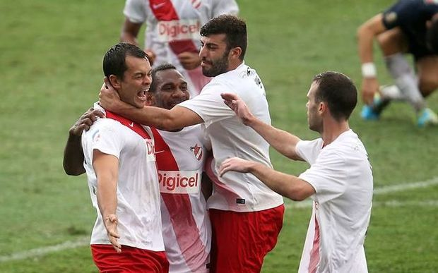 Amicale's Adam Dickinson celebrates with teammates after scoring the opening goal of the match.