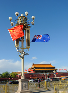 Chinese and New Zealand national flags flutter on a lamppost on the Tiananmen Square in Beijing, China.