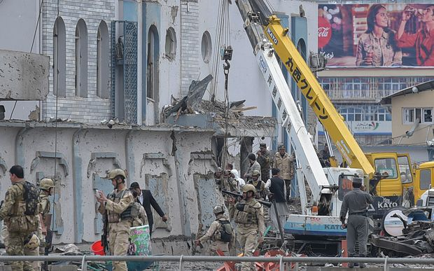 Afghan security personnel inspect the site of the car bomb attack.
