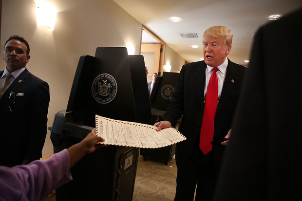 Donald Trump hands in his board of election card as he votes at his local polling station in New York's primary on April 19, 2016 in New York City.
