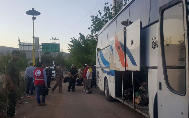 Syrians prepare to board as bus to leave the besieged town of Madaya, on 20 April.