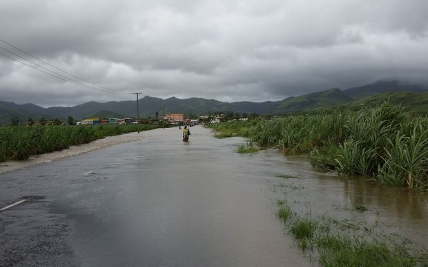 A flooded road with a person in distance wading through and sugar cane on either side.