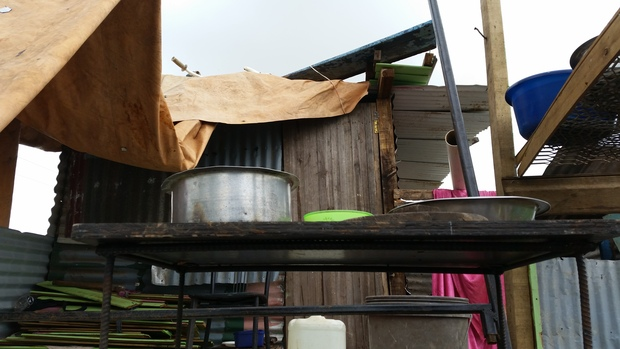 Tarpaulins draped over timbers supports and cooking pots in the open