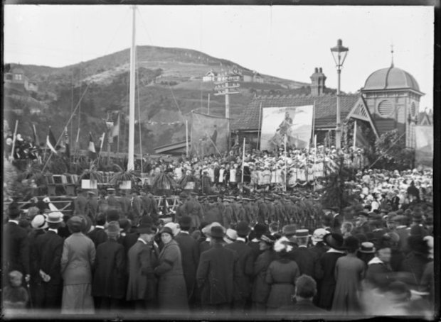 Anzac day commemoration at Petone, on 25 April 1916. Shows a crowd, flagpole and banners next to the Petone Railway Station. Photograph taken by Albert Percy Godber.
