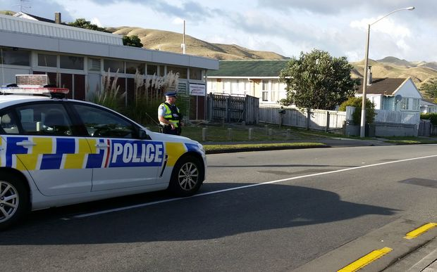 Police stand guard at the cordon on Warspite Avenue on Saturday morning.