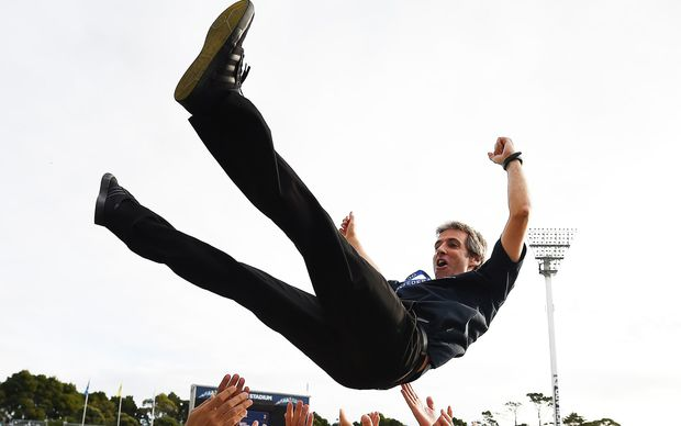 Auckland City coach Ramon Tribulietx is thrown skyward by in celebration.