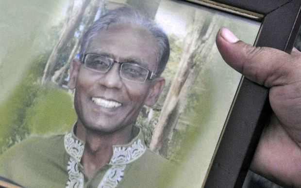 A man holds a portrait of Bangladeshi professor Rezaul Karim Siddique, who was hacked to death by unidentified attackers, in Rajshahi.