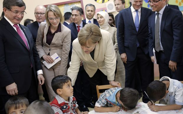 German Chancellor Angela Merkel (C) and Turkish Prime Minister Ahmet Davutoglu (L) talk with refugee children at a preschool, during a visit to a refugee camp on April 23, 2016 on the Turkish-Syrian border in Gaziantep.