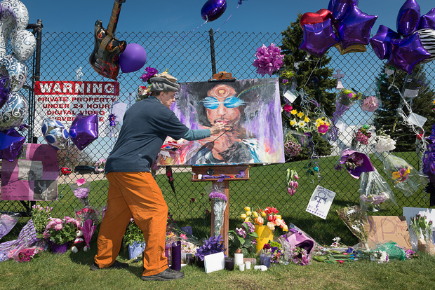 Prince fan Dan Carey contributes to a memorial outside of Paisley Park, Prince's home and studio, in Chanhassen, Minnesota.