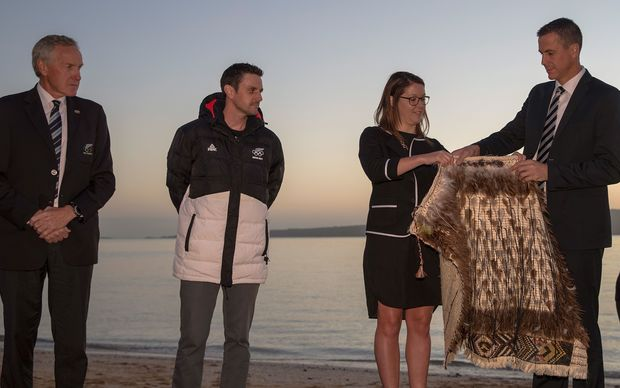 Chef de Mission Rob Waddell is handed the New Zealand Team kakahu (cloak) by Georgina Toomey with Former flagbearer and speed skater Shane Dobbin and Peter Wardell,
