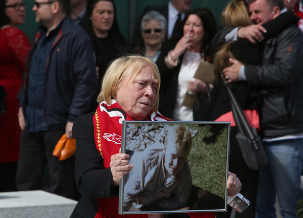 A woman holds an image of Keith McGrath, victim of the 1989 Hillsborough disaster.