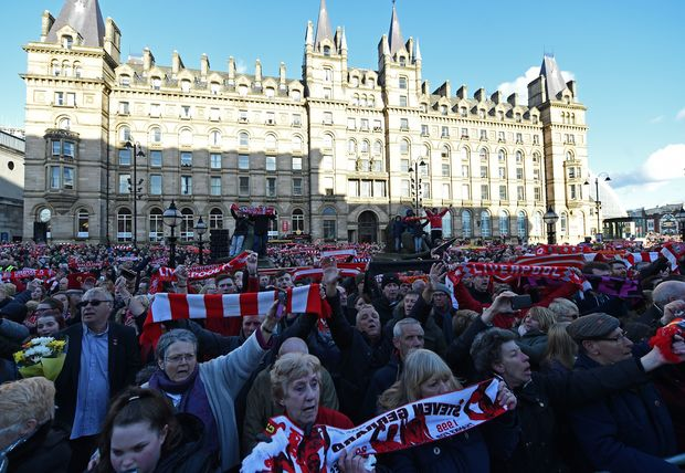 "People hold Liverpool football scarves in the air as they sing ""You'll Never Walk Alone"" outside St George's Hall in Liverpool."