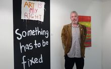 Leo stands beside artwork saying Art is My Right and Something has to be fixed