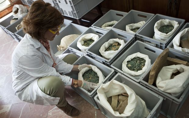 A woman opens a bag filled with Roman era bronze coins displayed at the archaeological museum in Seville.