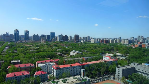View of downtown Beijing taken from a tall building showing modern skyscrapers and parks with tall green trees