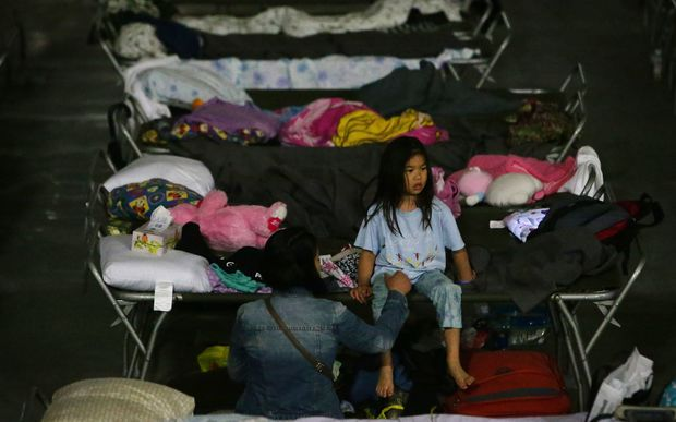 A young girl sits on a cot at a makeshift evacuee center in Lac la Biche, Alberta, 5 May, after fleeing forest fires north of Fort McMurray.