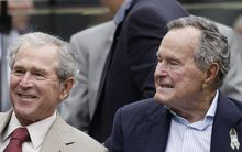 George W. Bush, left, and George H W  Bush at a NFL game in Texas in 2013.