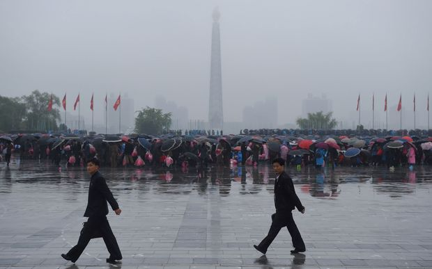 A crowd of people are seen on Kim Il-Sung Square before the Juche tower as rain falls in Pyongyang.