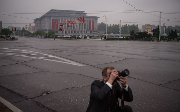 A foreign press photographer in front of the April 25 palace.