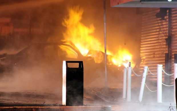 The car crashed into a group of shops and caught fire after it hit a gas main.