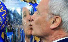 Leicester manager Claudio Ranieri is reflected in the silver as he kisses the EPL trophy.