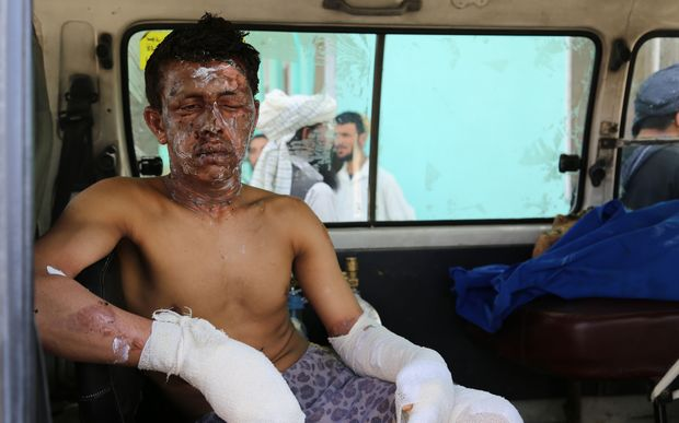 An injured Afghan man sits in an ambulance in Ghazni following the accident on the main Kabul-Kandahar Highway.