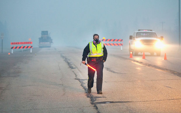 Smoke fills the air as a police officer stands guard at a roadblock along Highway 63 leading into Fort McMurray on May 8, 2016 near Fort McMurray, Alberta, Canada.