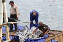 Indonesian police secure a vessel suspected of illegal fishing in West Papua waters.
