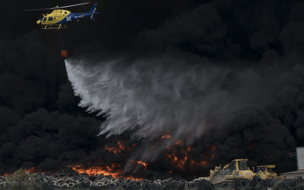 A helicopter drops water over tyres burning in an uncontrolled dump near the town of Sesena, Spain.