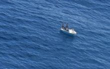 The three fishermen wave to the NZDF Orion.